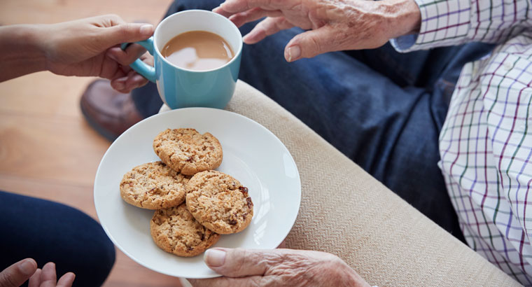 Older person with tea and biscuits