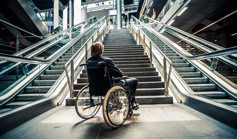 Man in wheelchair at the bottom of escalators.