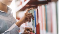 Woman reaching for book on library shelf