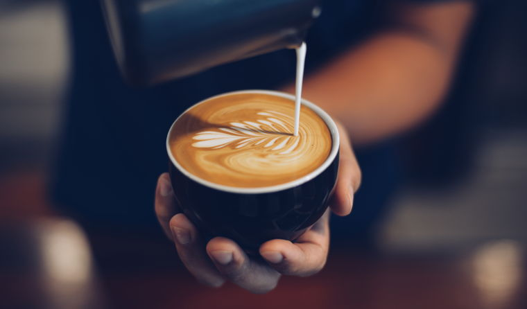Barista pouring a cup of coffee.