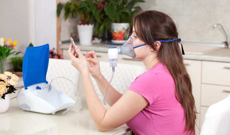 Young woman doing inhalation with a nebulizer at home to clear her airways.