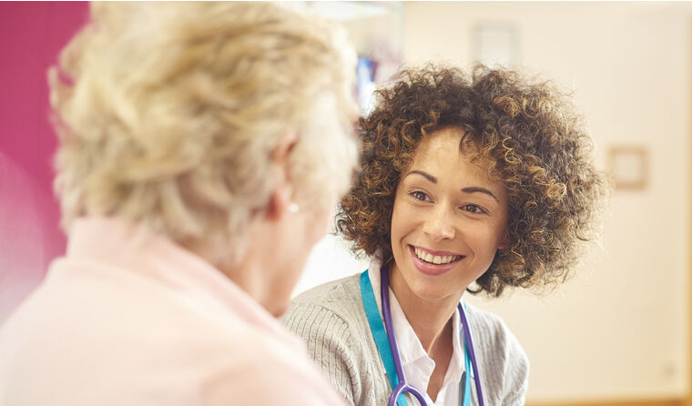 Female GP talking to middle-aged female patient