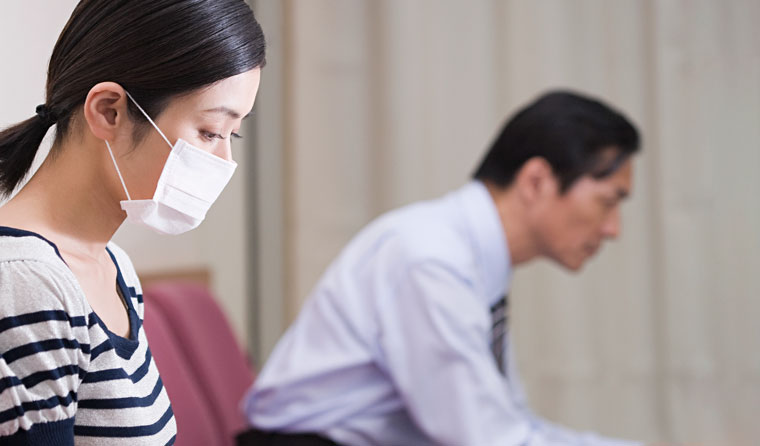 Patient with face mask in doctor's waiting room.